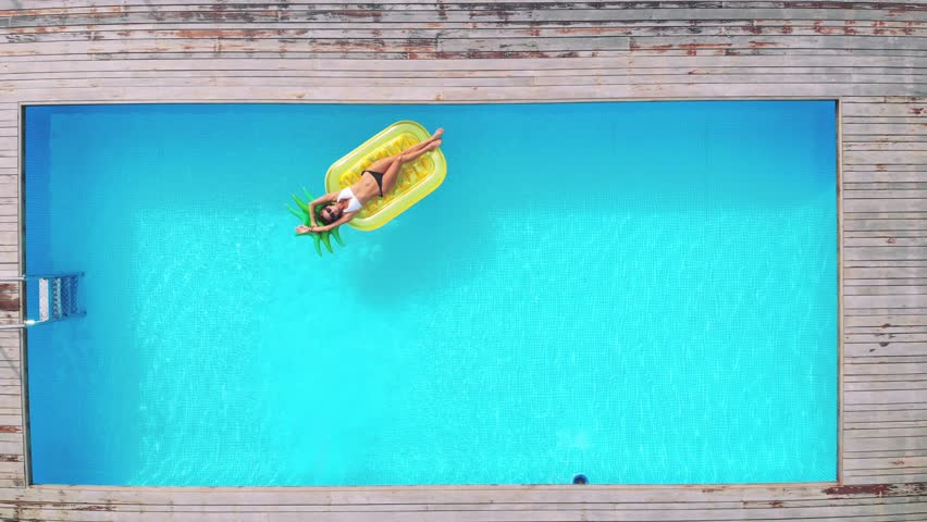 Aerial view of woman on pineapple shaped inflatable mattress in swimming pool. | Shutterstock HD Video #1022163919