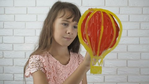 A child dreams of flying. Little girl draws a balloon.
