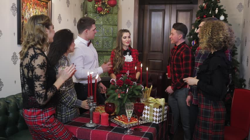 group of atractive young people aplause to woman which gets gift for the new year in tartan style