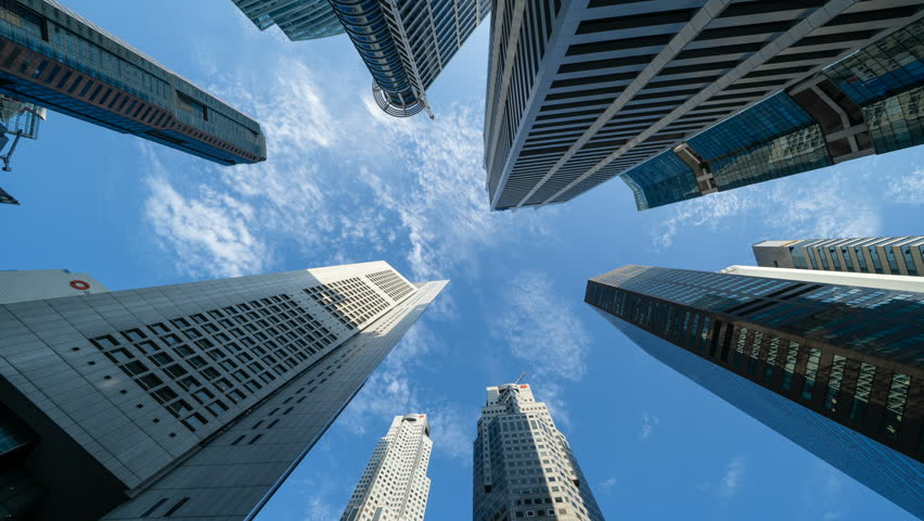 Looking up to high-rise buildings, skyscrapers, architectures in smart city for technology background in Singapore City with blue sky | Shutterstock HD Video #1022176861