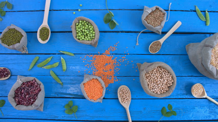 Legumes on wooden ecological background. Beans are located in unusual form on blue wooden table. Bean cultures in woven bags. Camera moves from right to left.    Shutterstock HD Video #1022202262