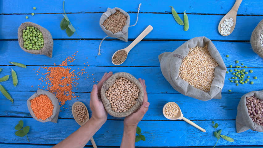 Legumes on wooden ecological background. Beans are located on a blue wooden table. Hands put woven bag with chickpeas on table.    Shutterstock HD Video #1022202400
