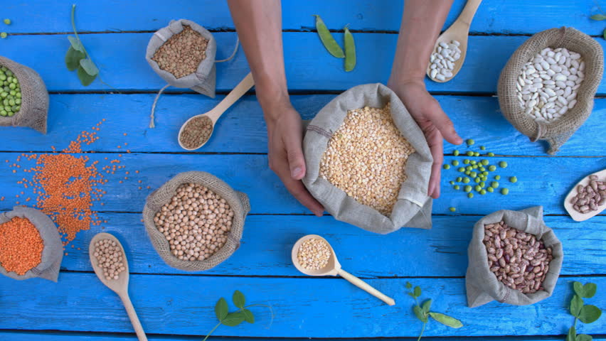 Legumes on wooden ecological background. Beans are on a blue wooden table. Hands take woven bag with peas from table.    Shutterstock HD Video #1022202523