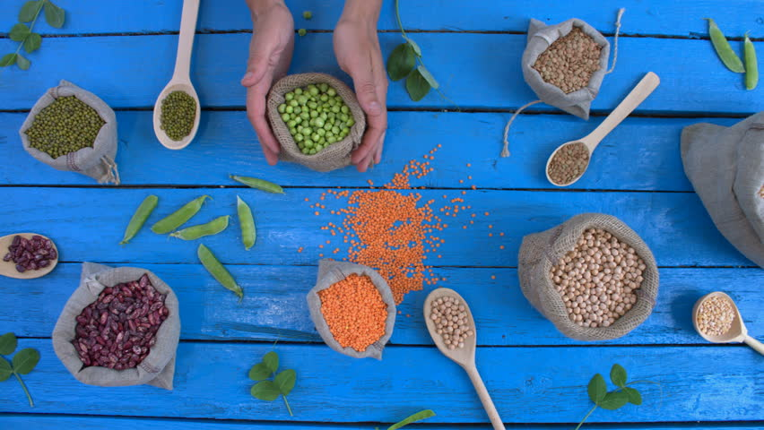 Legumes on wooden ecological background. Beans are on blue wooden table. Hands put woven bag with  green peas on table. | Shutterstock HD Video #1022202796