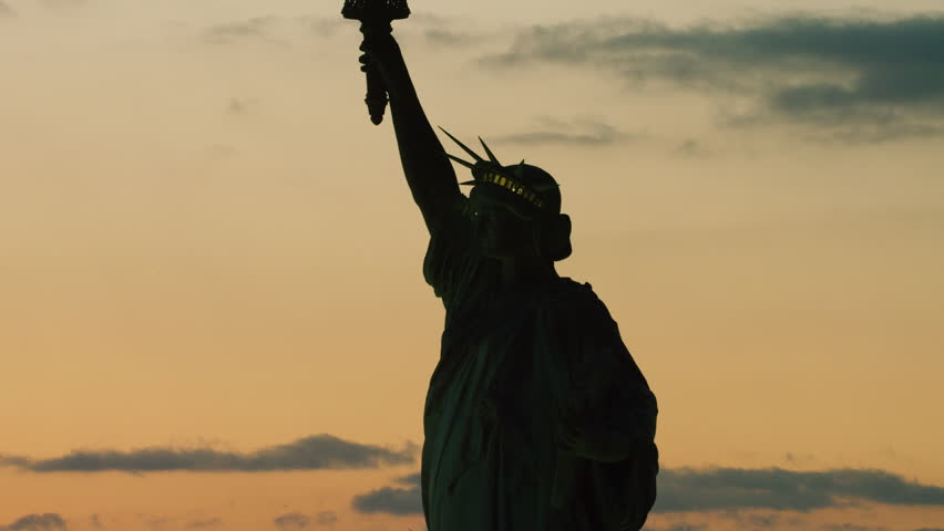 Establishing shot aerial view orbiting the Statue of Liberty on the East River, New York City, dark sunset light in winter. Shot on 4k RED camera on helicopter.