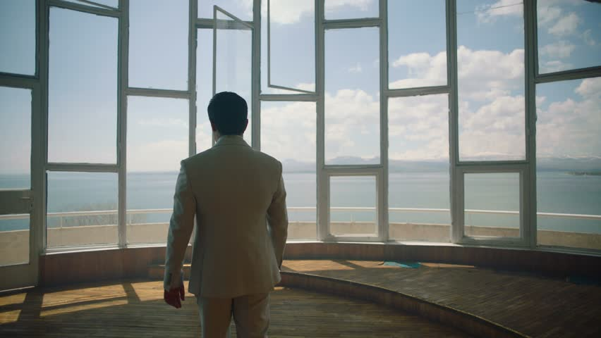 Businessman in a suit is walking towards a big window that looks at the sea . Back View of the Businessman wearing a Suit Standing in empty place . Shot on ARRI ALEXA cinema camera in slow motion . | Shutterstock HD Video #1022205076