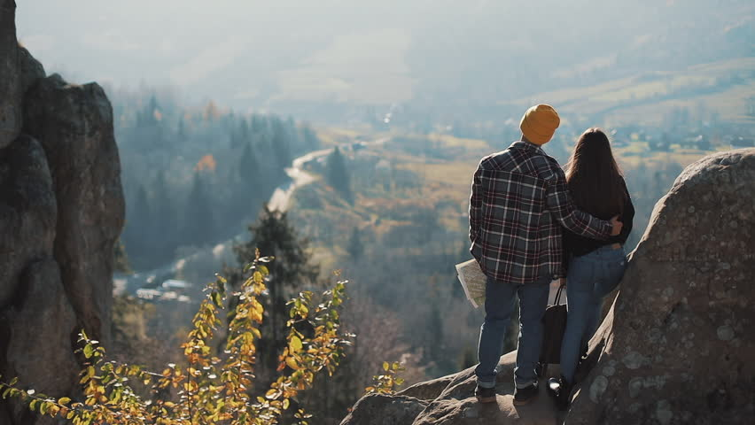 Young tourist couple in love standing on the rocks and enjoy a beautiful view. Man and woman visiting famous tourist attraction | Shutterstock HD Video #1022205130