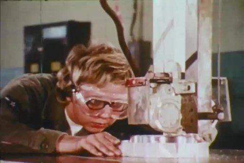 CIRCA 1971 - A machinist trainee gets trained on the job at a machine shop.