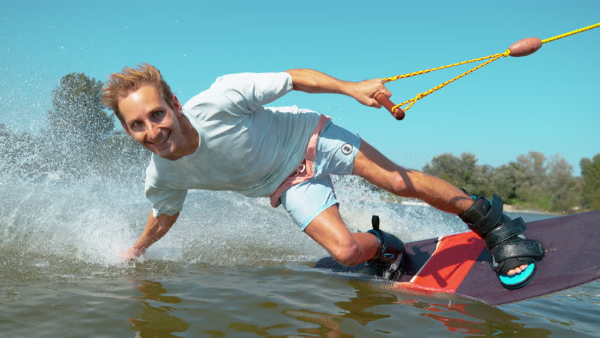 SLOW MOTION CLOSE UP Cheerful young surfer wakeboarding, sliding his hand on water surface, splashing water at camera. Smiling wakesurfer riding waterski cable park on sunny day. Wakesurfing in summer