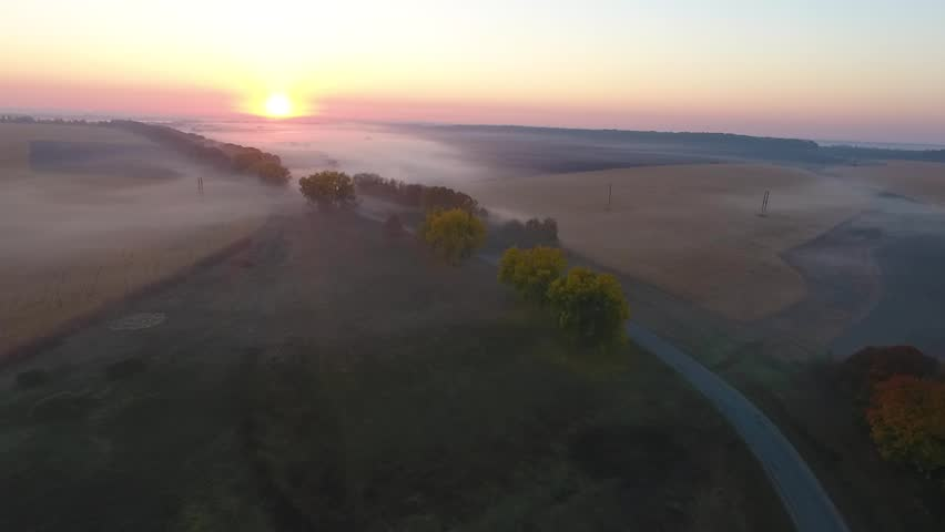 Beautiful aerial view of the road with driving car, morning fields covered with fog at sunrise. Ukraine | Shutterstock HD Video #1022232019