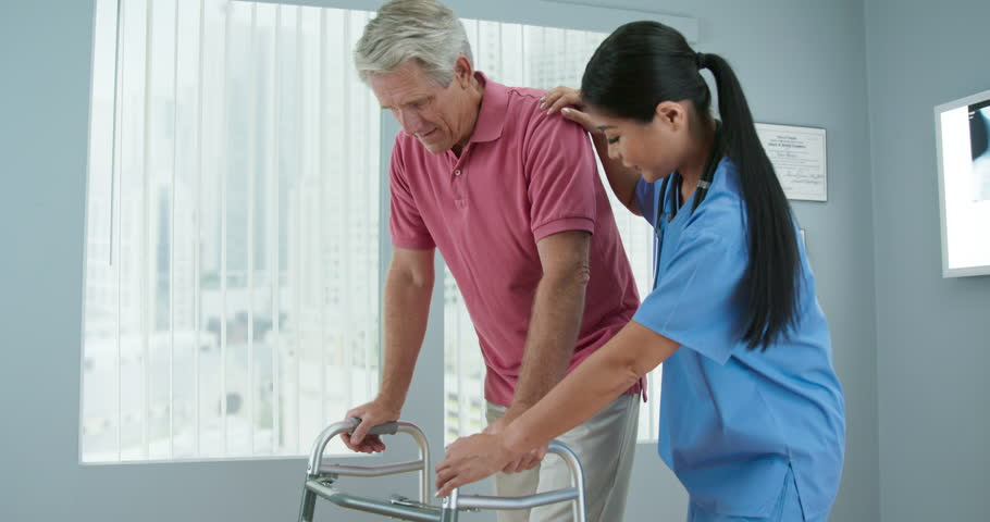 Senior Caucasian male patient learning to use walker with the assistance of Asian female physical therapist or nurse. Doctor helping older man walk again in recovery. Slow motion 4k