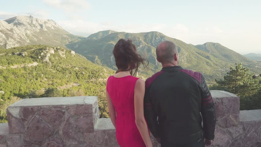 Close-up rear view of couple looking at mountains. Man in leather jacket with attractive woman on date in fortress overlooking mountains. Lovers together observing romantic view | Shutterstock HD Video #1022235763