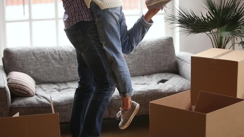 Happy couple first time buyers home owners embracing celebrating moving day, husband holding lifting wife among boxes after relocation into new flat, family goals, mortgage concept, close up view #1022264155