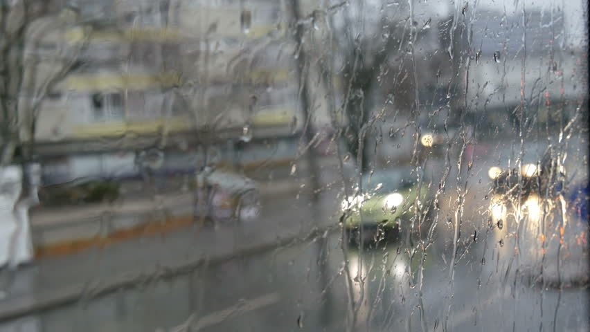 Close-up shot of rain drops and streaks on the window od moving bus by the city street in deep autumn | Shutterstock HD Video #1022289262