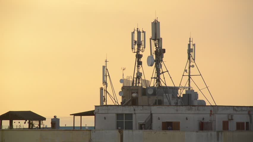 Radio, GSM mobile, telephone, satellite and TV antennas on the building. Antenna tower at the top of a building in Durres, Albania.