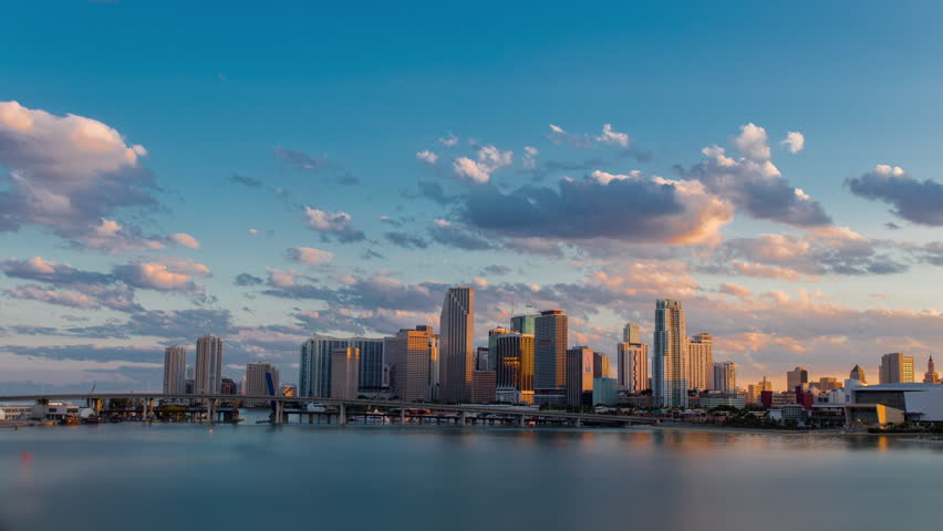 Day to night sunset timelapse hyperlaspe view of Miami downtown and Brickell skyline with I-95 Highway Bridge. Skyscrapers buildings in the back.