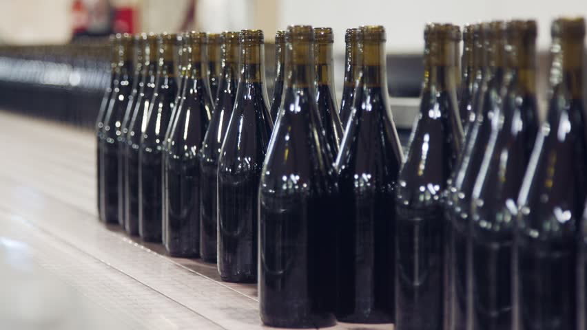Red Wine bottles on a conveyor belt in a wine bottling factory. | Shutterstock HD Video #1022319025