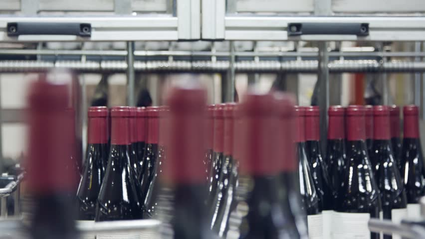 Red Wine bottles on a conveyor belt in a wine bottling factory. | Shutterstock HD Video #1022319106