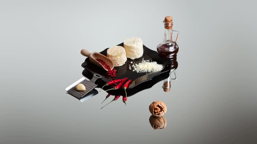 Art composition in the genre of still life with ricotta cheese, chilli peppers and a bottle of tincture. Five scenes on the mirror surface with delicious ingredients | Shutterstock HD Video #1022320597
