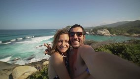 happy couple taking selfie photo in front of the sea in Tayrona National Park, Tropical Colombia. Crazy tourists travelling on the white beach of caribbean sea. 4K video