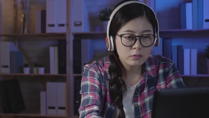 Slow motion girl student learning on line with headphones and laptop computer taking notes in notebook sitting at her desk at home in midnight. female nerd stay up late studying hard in dark room. | Shutterstock HD Video #1022338543