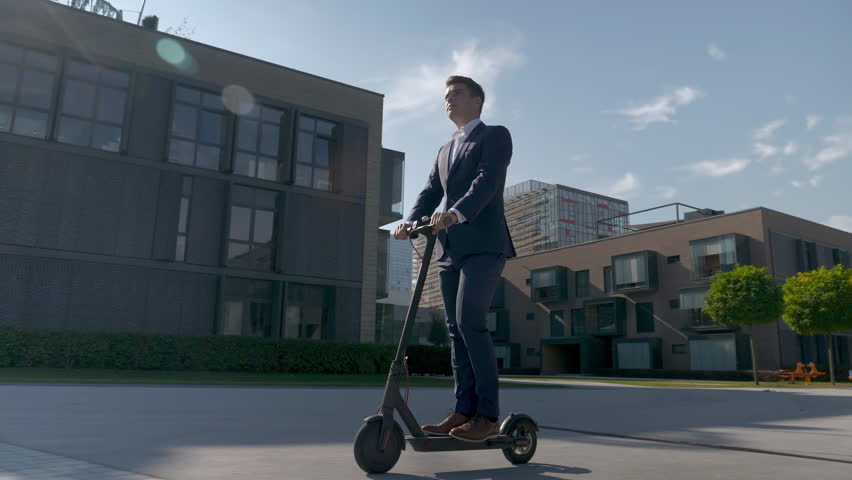 Slow motion - Adult businessman riding with electric scooter to work