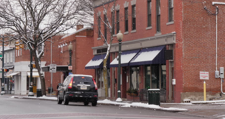 A long shot of a small American town's business district in the winter season. Pittsburgh suburbs. Snowing version. With audio.   Additional rights may be needed for commercial use.