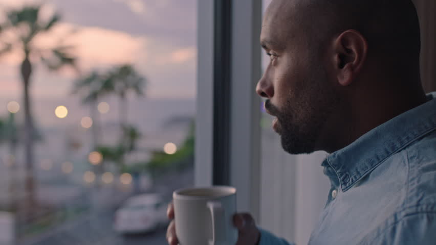attractive man drinking coffee looking out window in hotel room enjoying early morning view at sunrise contemplating future planning ahead #1022366008