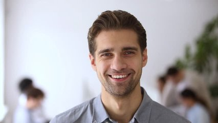 Young male team leader with smiling face posing in office, confident business executive ceo looking at camera, company employee, professional manager businessman, startup founder video portrait