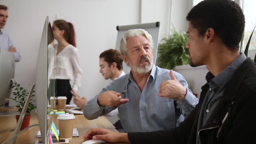Older male mentor helping teaching new employee explaining intern giving instructions in office, senior corporate leader teacher executive training young worker listening learning new skills at work   Shutterstock HD Video #1022373430