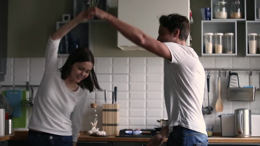Happy funny romantic young teen couple dancing to music in the kitchen cooking together having fun playful mood laughing enjoying preparing food feeling carefree, family at home weekend lifestyle  Royalty-Free Stock Footage #1022373463