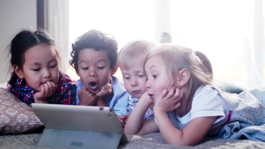 Cute little multiethnic boys and girls lying on bed at home and watching exciting video on digital tablet together Royalty-Free Stock Footage #1022389156