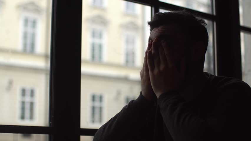 Young man sitting in cafe near window and look into distance. He's brooding, in a bad mood. Holding hands in front of face. Close-up #1022393317
