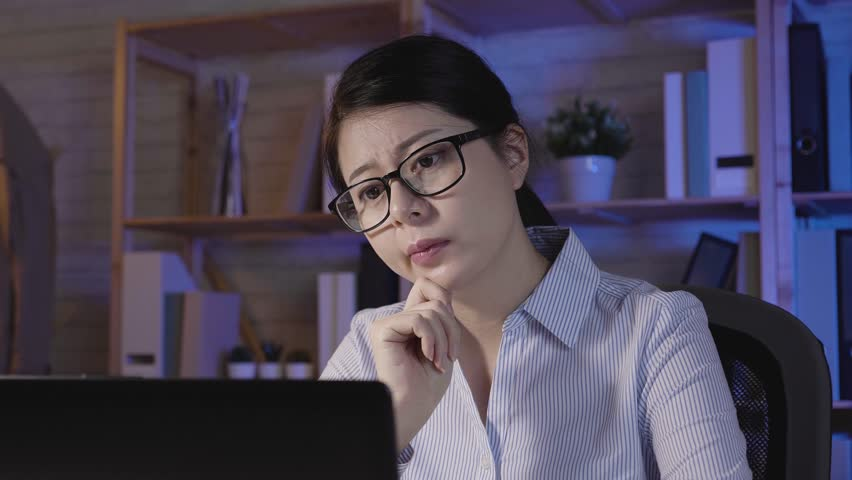 Slow action thoughtful young woman working on notebook computer at night in dark office. asian female designer works in late time. businesswoman thinking solve problem trouble of company using laptop | Shutterstock HD Video #1022399782
