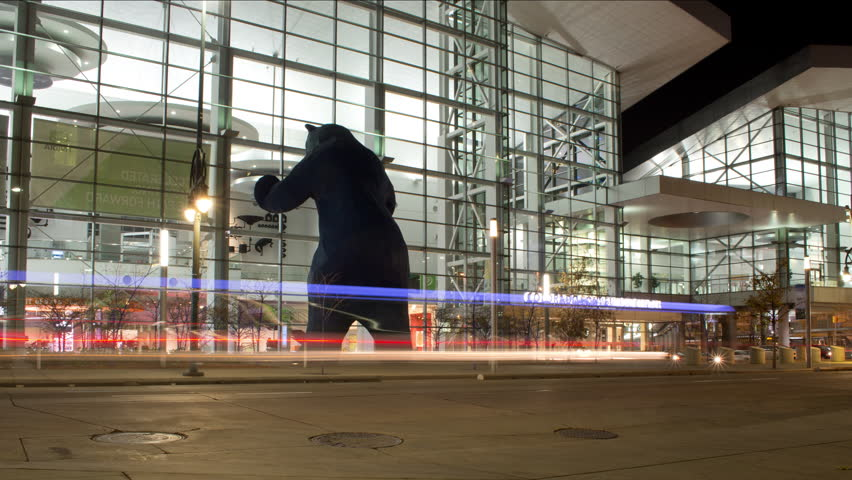 Denver, Colorado/United States - November 9, 2017 time lapse street view of the iconic giant blue bear sculpture in front of the Denver Convention Center entrance as cars and pedestrians pass at night