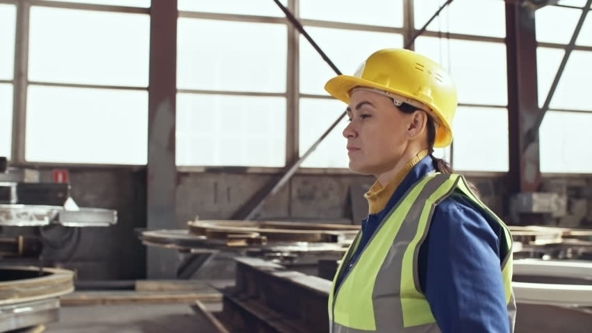 Tracking shot of middle-aged female engineer in hard hat walking through metal fabrication facility of steel plant #1022406994