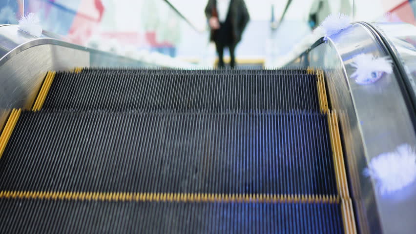 Shot of young man without bag moving on escalator, goes up the escalator in a big business center. Rush hour, subway underground station. Modern escalator stairs moving up.