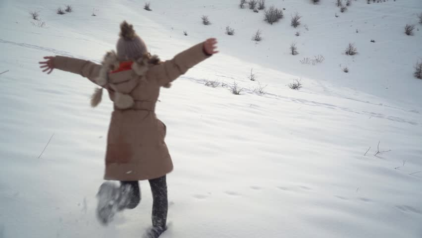 Young beautiful girl runs on the snow and jumps into it and starts making a snow angel. Slow motion video 100p