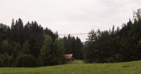 Suspension bridge in the mountains in summer. Beautiful landscape. Green trees.