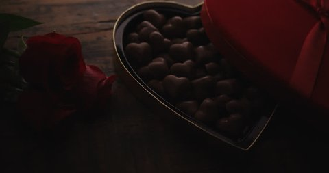 Heart shaped box of chocolate on wooden table with roses. Close-up with subtle camera movement.
