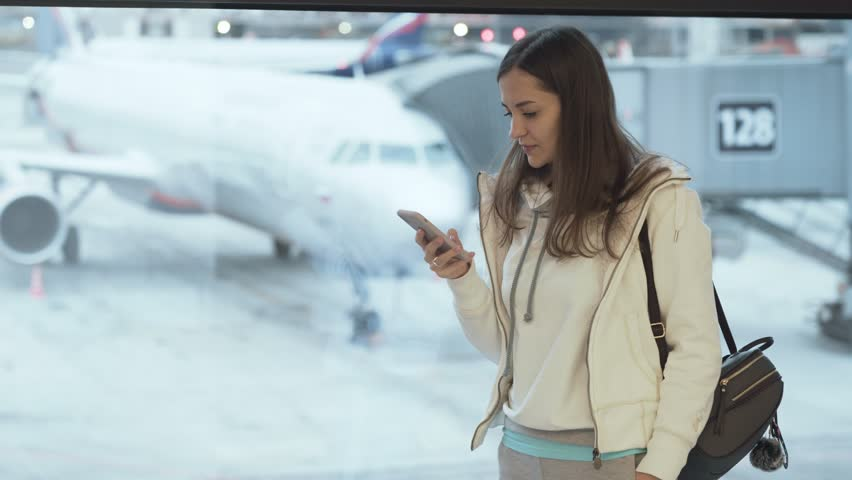 Girl in sportswear and with backpack standing at window in airport and talking on phone background of plane. Traveler female waiting her flight in lounge zone. Concept journey, terminal, trip #1022460010
