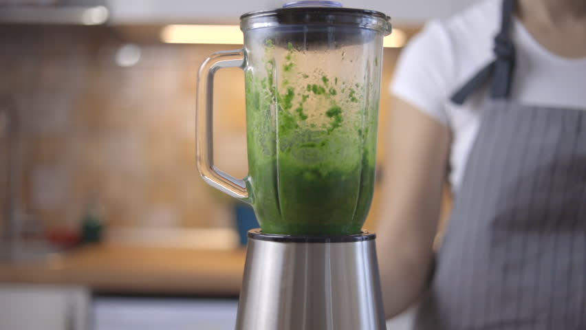 The process of preparing green smoothie in a kitchen blender. | Shutterstock HD Video #1022473294