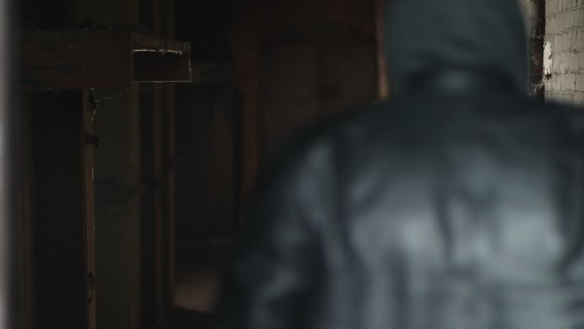 Dangerous man walking in an abandoned building. Thug smoking a cigarette walking away. | Shutterstock HD Video #1022478037