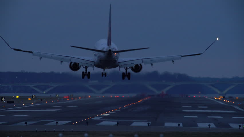 Real time long shot of a large jet airliner crabbing into the wind and landing away from the camera on a dark, windy, winter evening at Reagan National Airport in Virginia right next to Washington DC