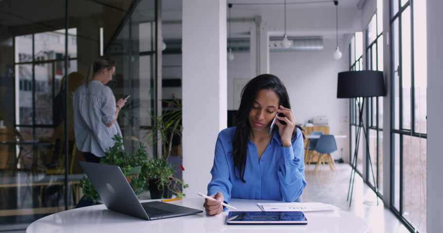 Dark skinned female employee talking on cellphone and checking information with stylus pencil on touch pad while her coworking colleague walking on background, Slow motion effect on 4K RED camera | Shutterstock HD Video #1022539297