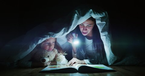 Slow motion of young mother is reading a goodnight story to her little daughter in the dark illuminating with a torch under the blanket. Concept of family, childhood, love, health, education