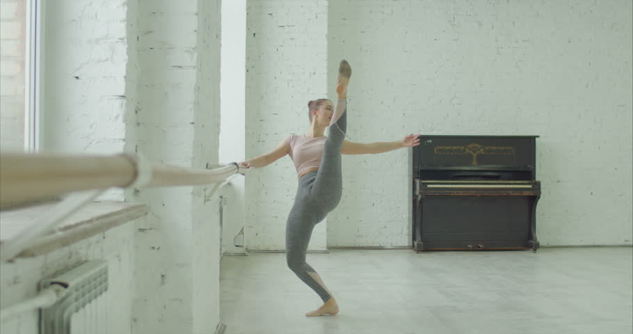 Elegant classic ballet dancer in sporty clothes rehearsing in ballet class. Beautiful ballerina with perfect body performing choreographic exercises, doing passe at ballet barre in dance studio. | Shutterstock HD Video #1022542330