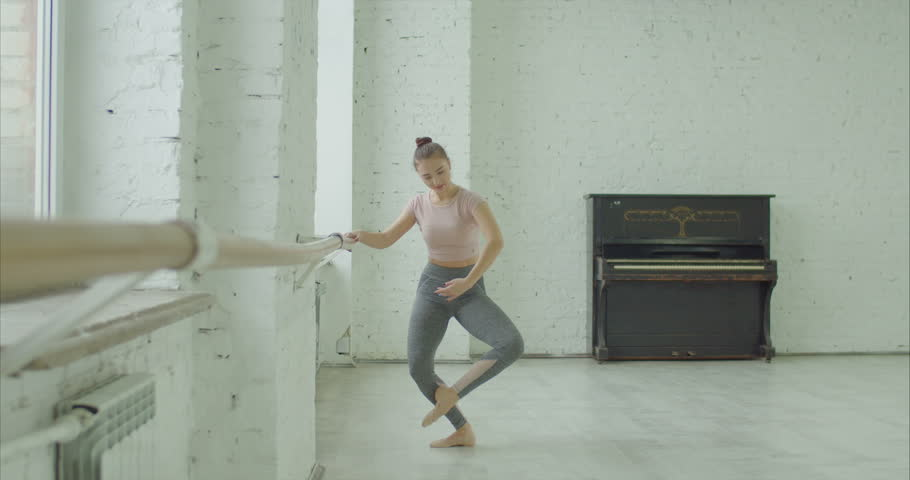 Elegant classic ballet dancer in sporty clothes rehearsing in ballet class. Ballerina with perfect body performing choreographic exercises, doing battement frapper at ballet barre in dance studio | Shutterstock HD Video #1022542360