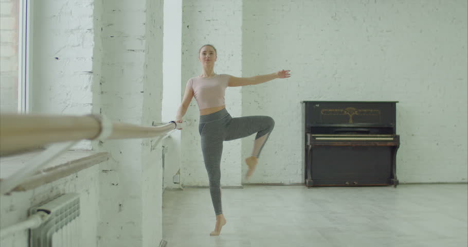 Elegant classic ballet dancer in sporty clothes rehearsing in ballet class. Beautiful ballerina with perfect body performing choreographic exercises, doing dehors at ballet barre in dance studio. | Shutterstock HD Video #1022542366