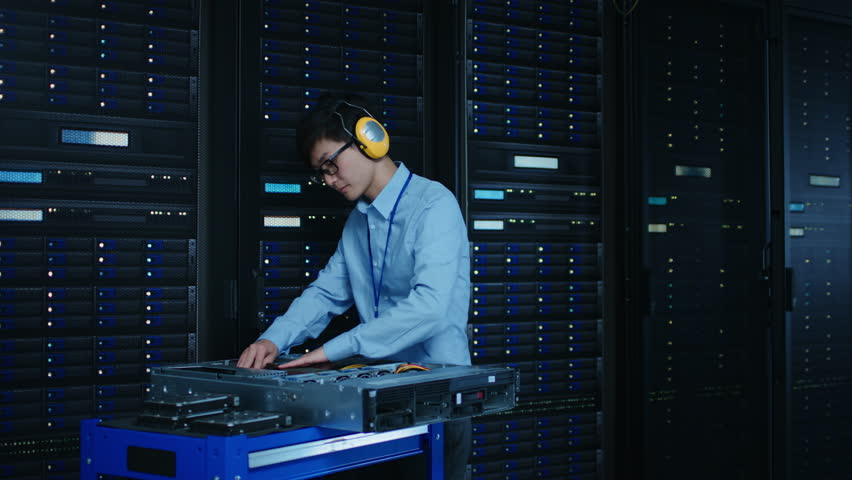 In the Modern Data Center: IT Technician Wearing Protective Headphones Working with Server Racks, on a Pushcart Installing New Hardware. Engineer Doing Maintenance and Diagnostics of the Database. | Shutterstock HD Video #1022552575